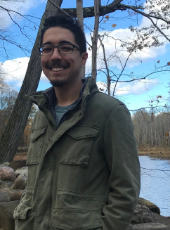 Student standing on a bridge during fall